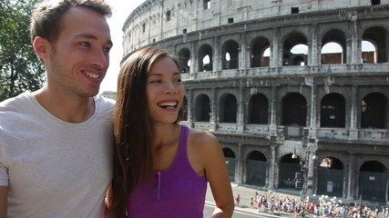 Aufkleber - Couple in Rome by Colosseum talking and looking in Italy. Happy young friends traveling and sightseeing having fun in front of Coliseum. Love and travel concept with multiracial couple.