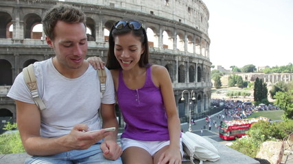 Aufkleber - Couple in Rome by Colosseum using smartphone looking at pictures or using travel app in Italy on smart phone. Happy lovers on honeymoon sightseeing Coliseum. Travel concept with multiracial couple.