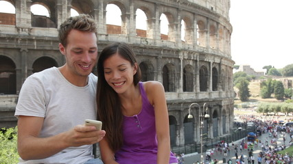 Aufkleber - Travel couple taking selfie photo by Colosseum, Rome, Italy. Smiling young romantic couple traveling in Europe taking self portrait picture with smartphone camera in front of Coliseum. Man and woman.