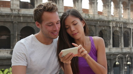 Aufkleber - Rome couple by Colosseum using smartphone looking at pictures or using travel app in Italy. Happy lovers sightseeing Coliseum using smartphone. Love and travel concept with multiracial couple.