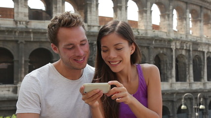 Aufkleber - Couple in Rome by Colosseum using smart phone looking at pictures or using travel app in Italy. Happy lovers on honeymoon sightseeing Coliseum. Love and travel concept with multiracial couple.