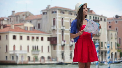 Wall Mural - Travel tourist woman holding map in Venice, Italy. Girl on vacation smiling happy by Canal Grande. Mixed race Asian Caucasian girl having fun traveling outdoors during holidays in Europe.