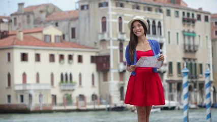 Wall Mural - Travel woman tourist traveling in Venice, Italy holding map. Asian girl on vacation smiling happy by Grand Canal. Mixed race Asian Caucasian girl having fun during holidays in Europe.