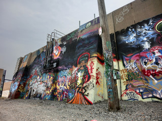Urban wall with lots of painted color and graffiti - landscape color photo