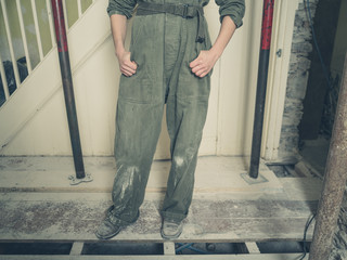 Person in boiler suit in house undergoing renovations