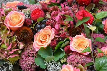 Herbstliche Blütendekoration / Blumendekoration mit Hortensienblüten, Rosenblüten, Fetthenne, Beeren und Blattgrün formatfüllend - üppig blühend - füllig