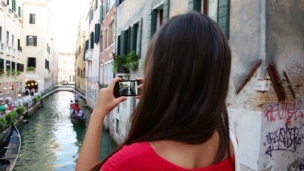 Wall Mural - Woman tourist taking picture photo in Venice, Italy. Travel girl using smartphone taking pictures of canal and gondola during vacation holidays in Europe.