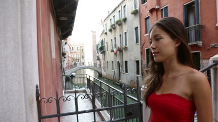 Wall Mural - Venice, Italy - woman in dress walking by canal over bridge smiling in Venice. Tourist girl in her 20s. Mixed race Asian Caucasian female model outside.