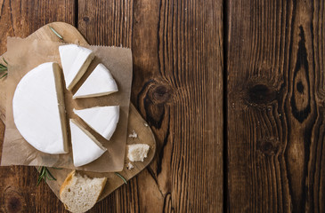 Pieces of Camembert on wooden background