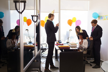 Woman Celebrates Birthday Party In Business Office With Coworker