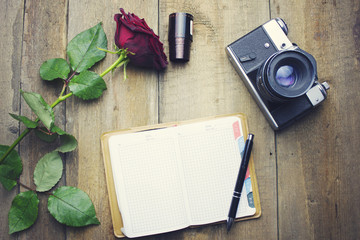 rose, camera and notebook on table
