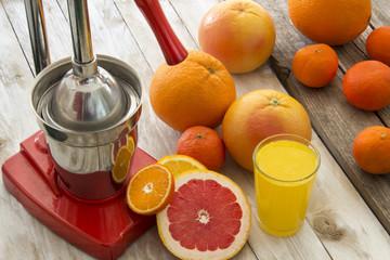 Orange juice, citrus slices and press juicer on wooden table