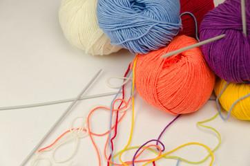 Balls of colored yarn, knitting needles