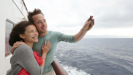 Wall Mural - Cruise ship couple taking selfie self portrait photo romantic. Happy lovers, woman and man traveling on vacation travel sailing on open sea ocean enjoying romance. Young Asian woman and Caucasian man.