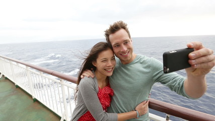 Aufkleber - Cruise ship couple taking selfie self portrait photo romantic. Happy lovers, woman and man traveling on vacation travel sailing on open sea ocean enjoying romance. Young Asian woman and Caucasian man.