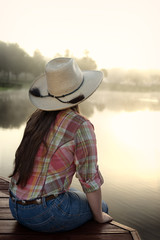 Girl woman lady with long dark brown hair sitting on a lake pond dock with reflections at sunrise or sunset in cowboy hat flannel shirt looking relaxed happy serene beautiful young  peaceful