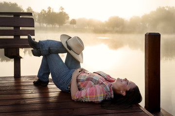 Girl woman lady with long dark brown hair lying down on a lake pond dock with reflections at sunrise or sunset in cowboy hat flannel shirt looking relaxed happy serene beautiful young  peaceful