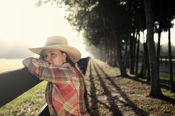 Cowgirl woman in cowboy hat flannel shirt and jeans leaning on country rural fence looking confident happy serene smart alone waiting watching patient