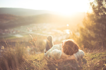 arefree happy woman lying on green grass meadow on top of mountain edge cliff enjoying sun on her face.Enjoying nature sunset.Freedom.Enjoyment.Relaxing in mountains at sunrise.Sunshine.Daydreaming Wall mural