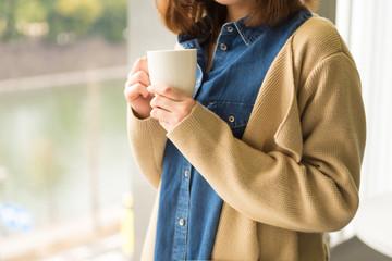 コーヒーカップを持つ20代女性