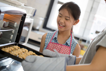 Happy little Asian cute chef looking cookies from oven