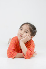 Little Asian girl lying on the floor on isolated