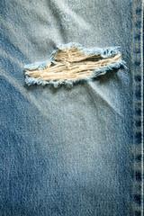 Torn old blue jeans background.