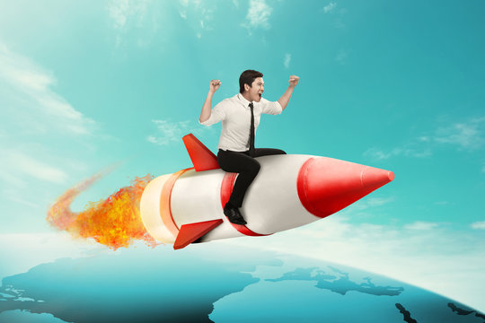 Business man riding rocket across the earth