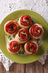Baked rolls with salami in the form of roses close-up. Vertical top view