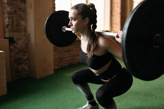 Strong woman lifting barbell at the gym