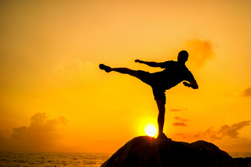 Silhouette of a man doing exercises on rocks by the sea at dawn