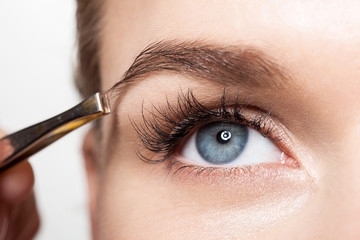 Closeup of a woman making a shape eyebrows with tweezers