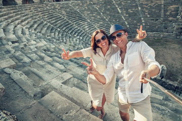 Positive young couple take a self photo in antique amphitheter i