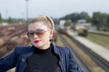the woman's portrait in sunglasses against railway tracks