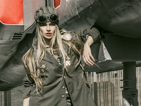 beautiful girl in military uniform with military equipment
