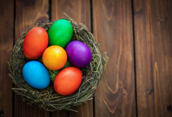 colorful Easter eggs in the nest on the old wooden background