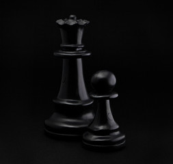 Chess. Black Pawn and Queen on black background.