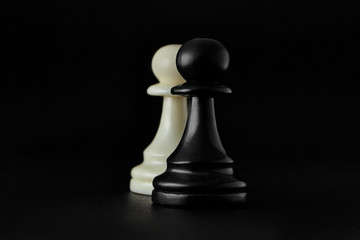 Chess. Black and White pawns on the black background. Pawns, infantry chess.