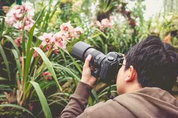 Asian man  taking photo beautiful orchid flowers in a orchid house