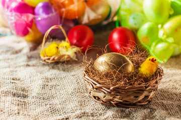 Close up of golden easter egg and chicken in small basket, with