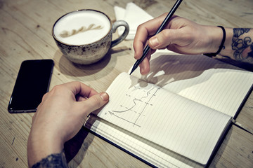 Close-up view of male hands with note book and coffee draw diagramms