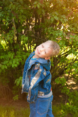 Smiling beautiful child face. 7 years old kid dressed in casual blue jeans clothes standing at green nature background with hands in pockets. Portrait of beautiful little boy looking at camera.