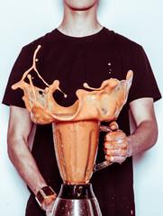 Man holding splashing blender