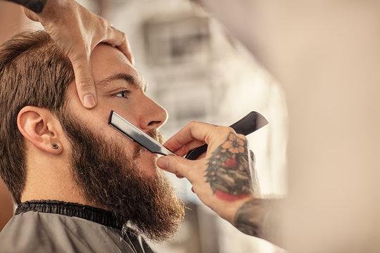 Barber with old-fashioned black razor.