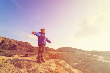 little boy with backpack travel in mountains