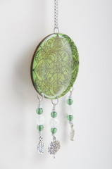Photo of hand-painted pendant on a wood base, using epoxy resin, glass beads and metal accessories. In green color