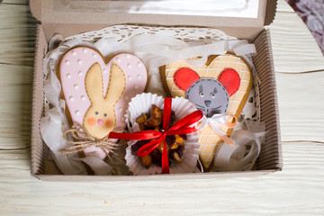 a collection of gingerbread cookies in the shape of a heart, muffins and animals on a white wooden background