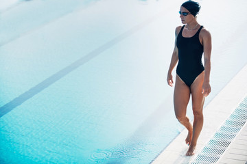 Swimming athlete walking by the pool