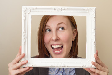 Happy smiling beautiful woman looking through a white picture frame.