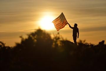 Man Holding a USA Flag on a Hill